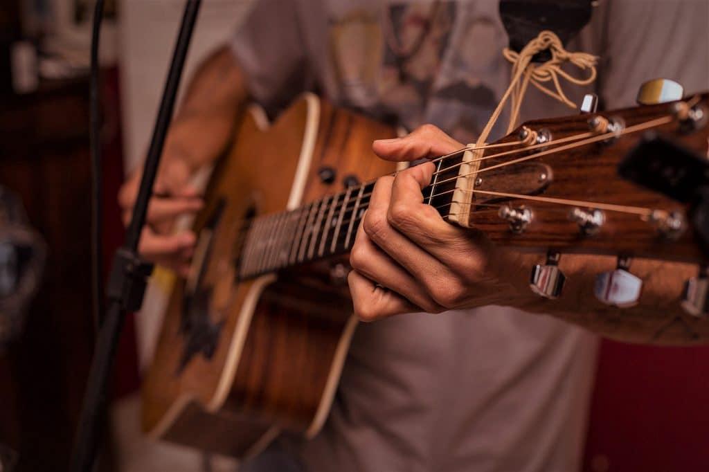 Guitarist plays steel-string acoustic guitar