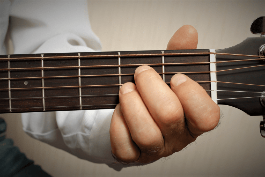 Person with Short Fat Fingers playing the guitar