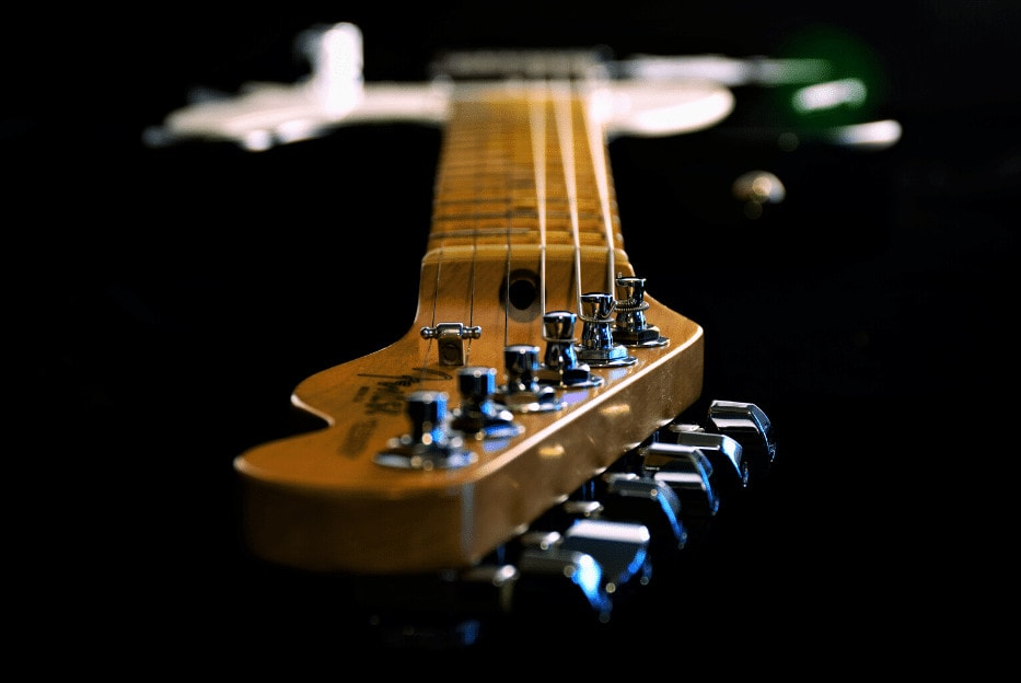 photo shows readers a headstock and neck of a guitar and electric guitar stings