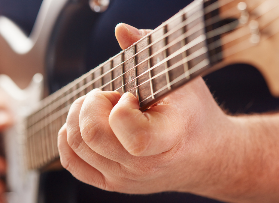 photo displays a guitar and guitarist with fat fingers